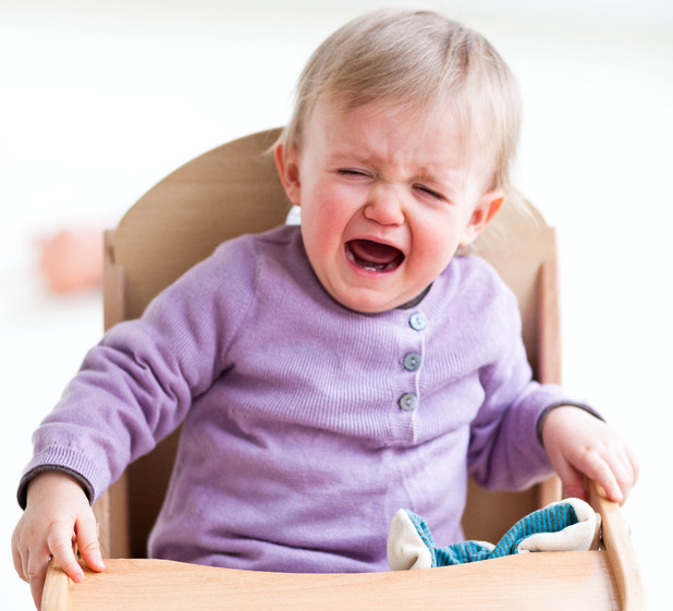 Baby crying in high-chair.