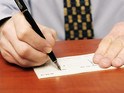 Stock image of man writing cheque