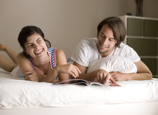 stock image of man and woman reading magazine together