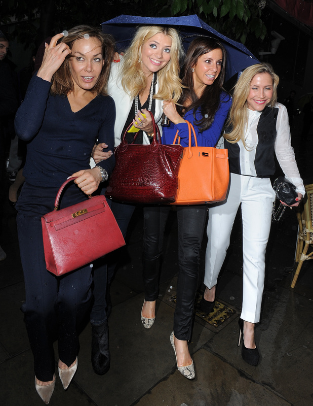 Holly Willoughby, Heidi Range, and Tara Palmer-Tomkinson enjoy a night out at the theatre together. It was pouring with rain, so the trio huddled under one umbrella