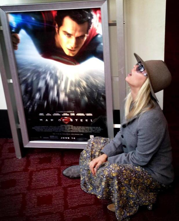 Kaley Cuoco poses next to Man Of Steel poster