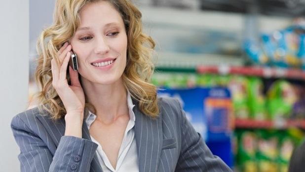 Woman talking on phone at till