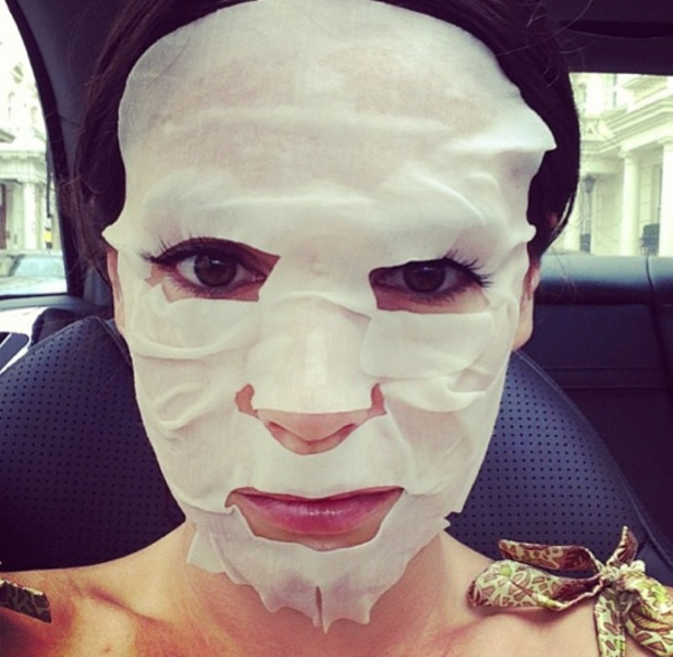 Kelly Brook in the back of a taxi wearing a paper Shu Uemura face mask, 16 July 2013