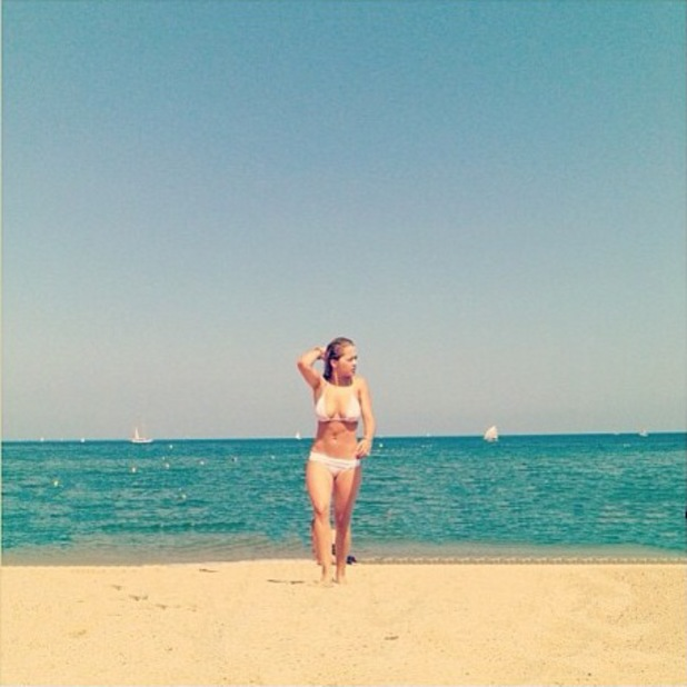 Rita Ora pictured on the beach wearing a white bikini in a picture she posted on twitter