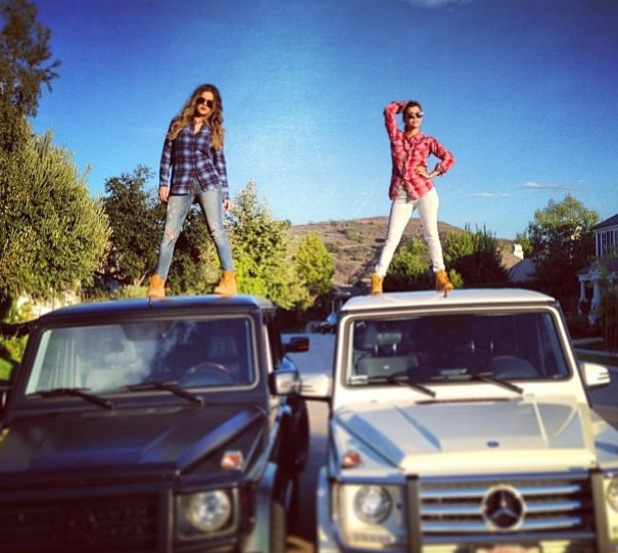 Khloe and Kourtney Kardashian stand on their cars in checked shirts - 20 August 2013