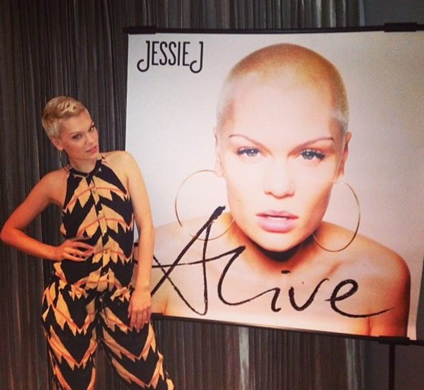 Jessie J posing alongside a large poster of her second studio album, Alive.