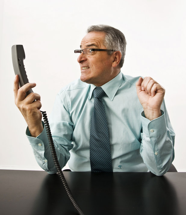 Model Released - Businessman looking angry at a phone receiver in his hand 2000s