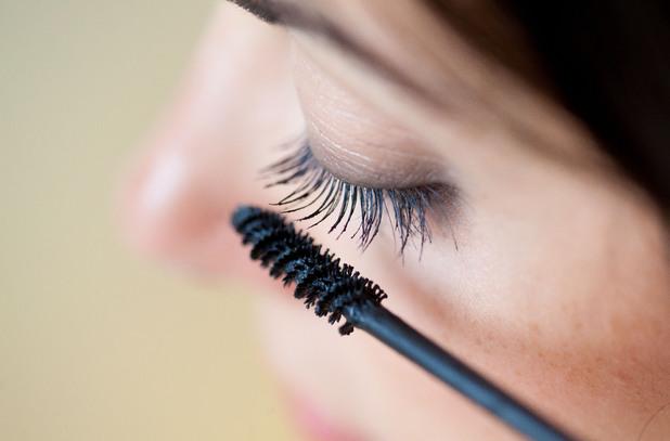 Woman applying mascara on her eyelashes. 5 Oct 2012