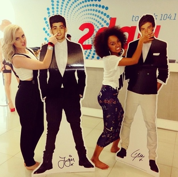 Little Mix's Perry Edwards and Leigh-Anne Pinnock posing alongside cardboard cutouts of One Direction's Zayn Malik and Liam Payne