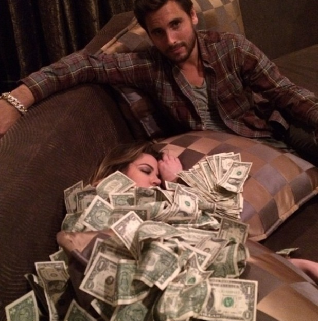Khloe Kardashian covered in money next to Scott Disick - 2013