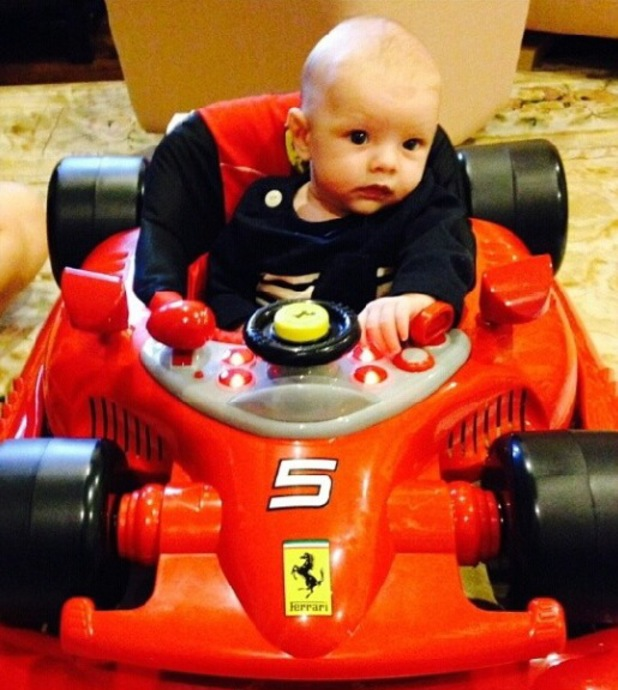 Josh Duhamel and Fergie's baby son Axl sit in red Ferrari racing car.