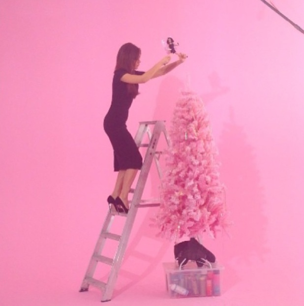Victoria Beckham puts the finishing touches to her pink festive Christmas tree
