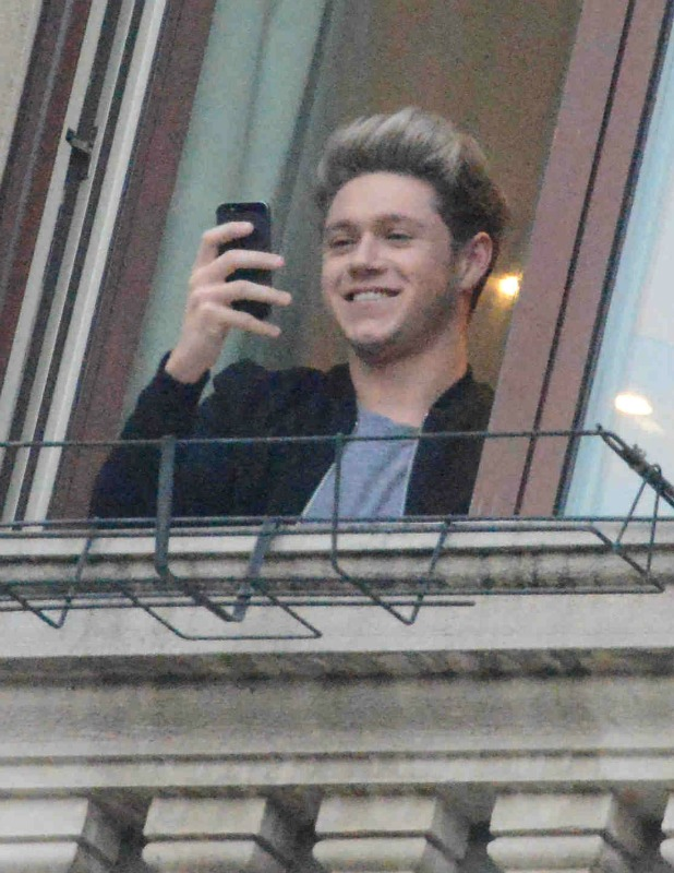 Niall Horan looks at crowds of devoted One Direction fans outside their hotel in Milan, Italy, 12 December 2013