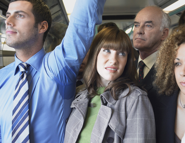 Woman tries to avoid a man's sweaty armpit on a crowded train for survey that reveals our pet hates when it comes to commuting