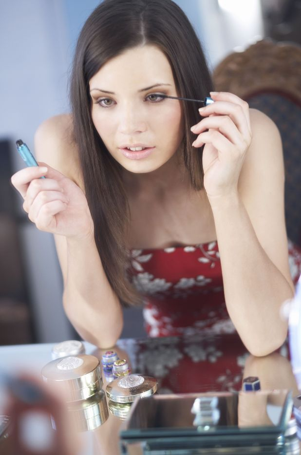 Woman putting on mascara in mirror for piece on women spend an hour a day on their appearance