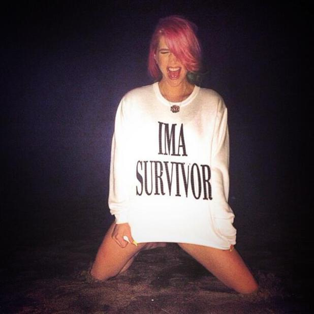 Kesha leaves rehab and poses in a 'survivor' T-shirt in the sand, 7 March 2014