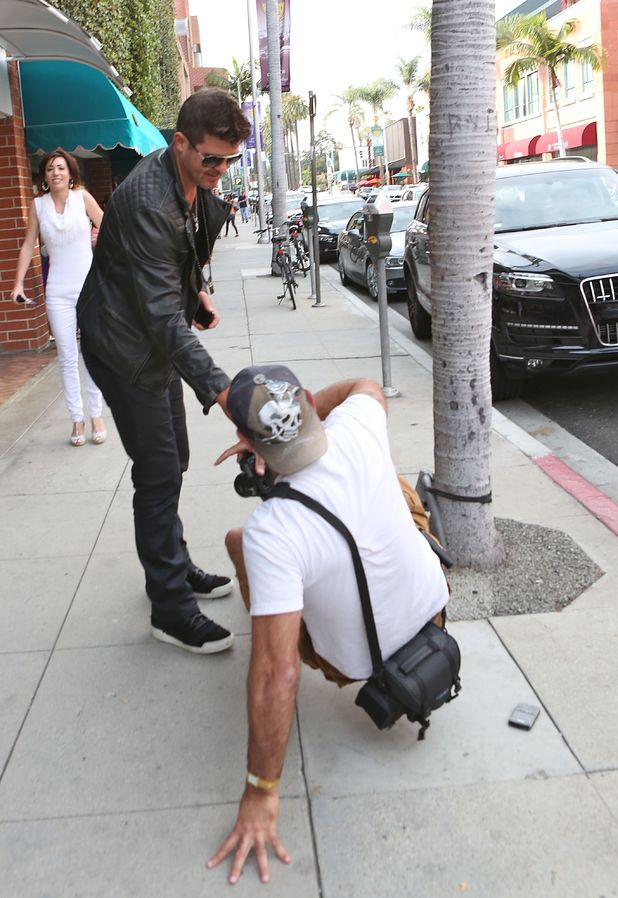 Robin Thicke helps up a fallen photographer to his feet after falling to the ground in LA - 11.3.2014