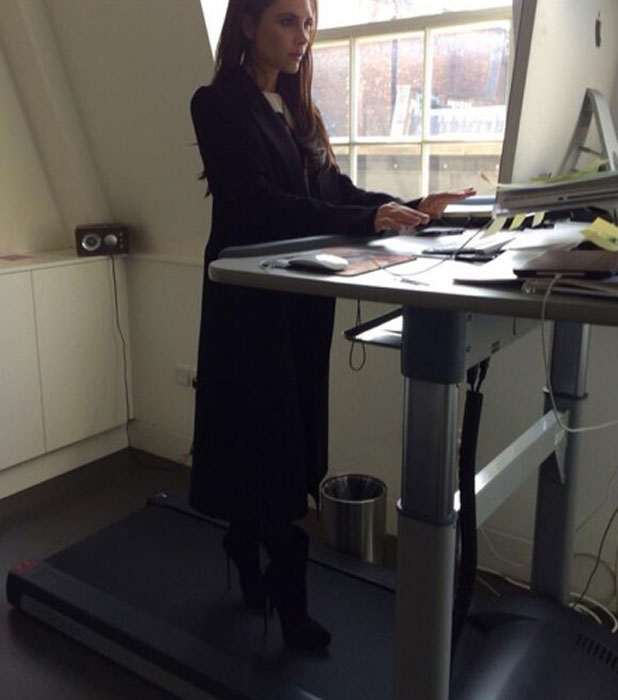 Victoria Beckham wears heels on an office desk / treadmill in London, 12 March 2014