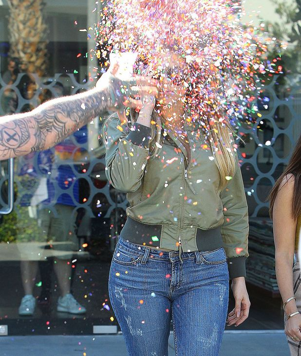 Kourtney and Khloe Kardashian get confetti thrown at them by a tattooed clown, 11 Apr 2014