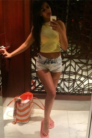TOWIE's Jasmin Walia poses in blue denim shorts and a yellow top while on holiday in Dubai - 20 April 2014