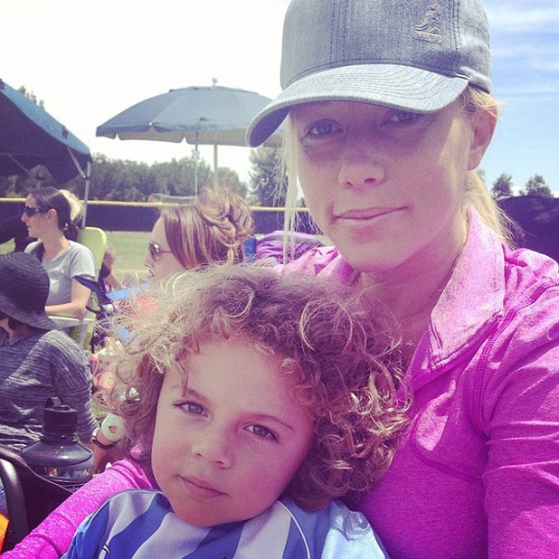 Kendra Wilkinson cuddles up to son Hank Baskett Jr after his football game, Los Angeles, 27 April 2014