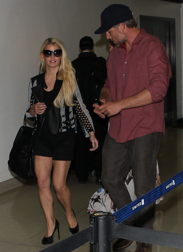 Jessica Simpson in short black skirt and leather jacket, arrives at Los Angeles International Airport (LAX) holding hands with with partner Eric Johnson, 4 May 2014