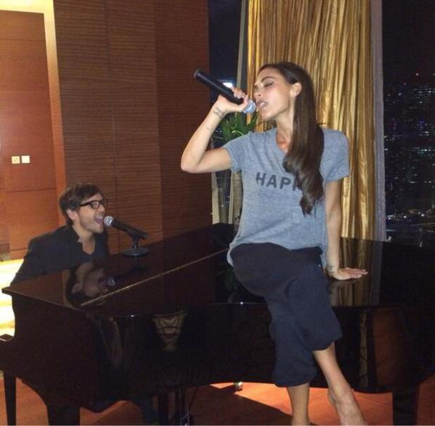 Victoria Beckham sings with hairstylist Ken Paves on a microphone (10 May).