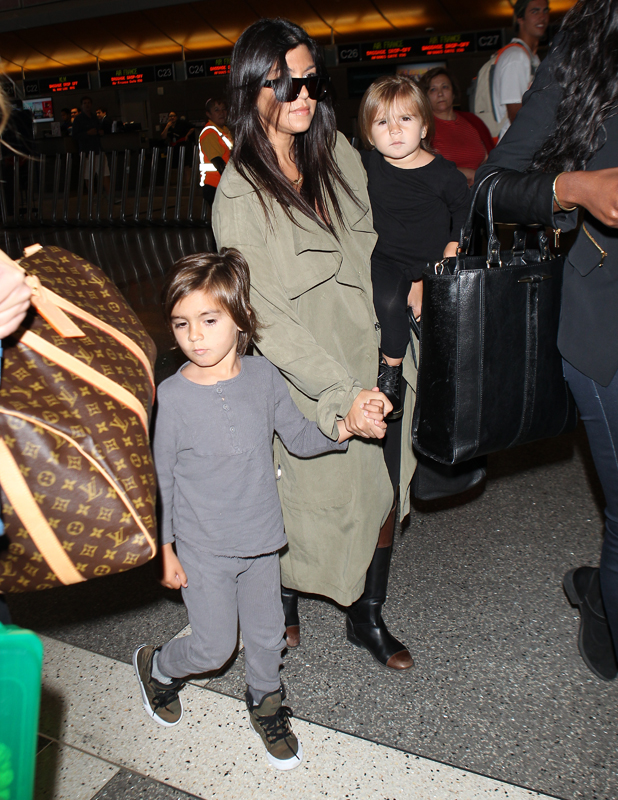 Kourtney Kardashian carrying daughter Penelope Disick and holding hands with son Mason Disick as they arrive at Los Angeles International (LAX) Airport, 18 May 2014