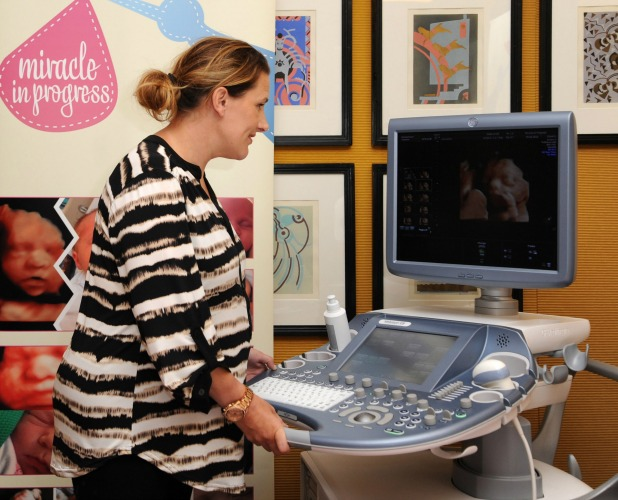 Sam Bailey poses with a scan of her baby at the launch of 'Miracle In Progress' high definition baby scans, 17 June 2014