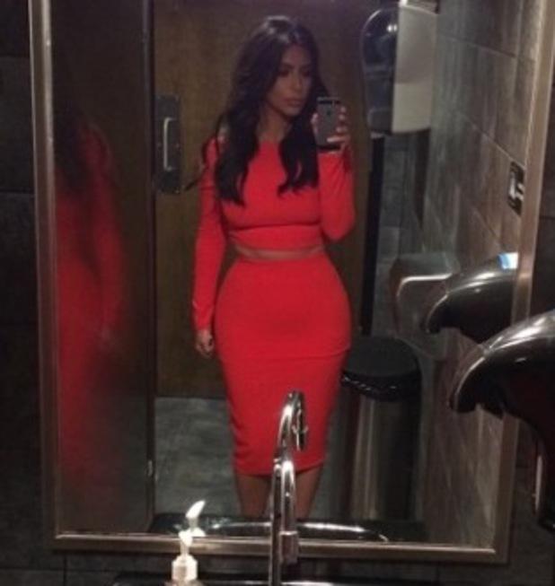 Kim Kardashian wears hair in old skool curls and Kardashian Kollection red skirt and top - 8 July 2014
