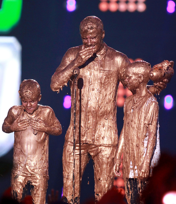 David Beckham (C) with Cruz Beckham (L) and Romeo Beckham (R) get slimed at the Nickelodeon Kids' Sports Choice Awards, LA 17 Jul 2014