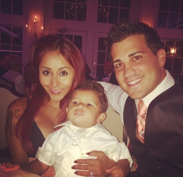 Snooki poses with fiancé Jionni LaValle and son, Lorenzo at a wedding, 18 July 2014