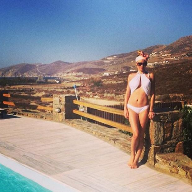 Chloe Sims poses in a white bikini in Mykonos, 10 August 2014