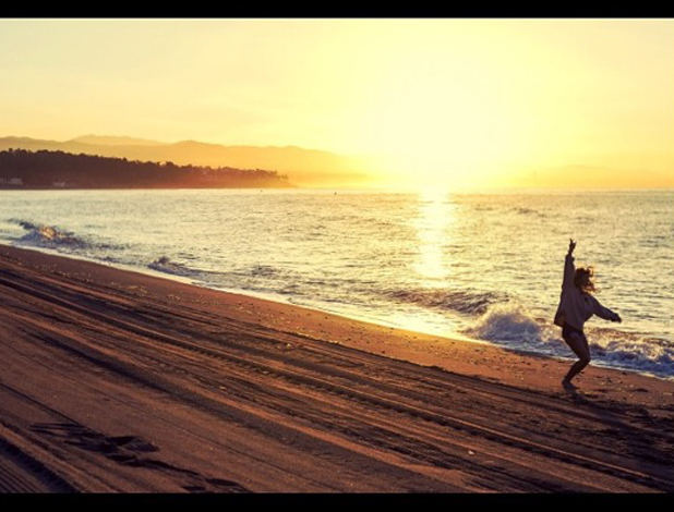 Cheryl Fernandez-Versini runs along a beach in picture captioned: 'I don't care', 22 August 2014
