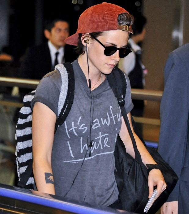 Kristen Stewart arrives at Narita International Airport to catch a flight wearing a t-shirt emblazoned with the slogan 'It's awful I hate it!' 29 August 2014