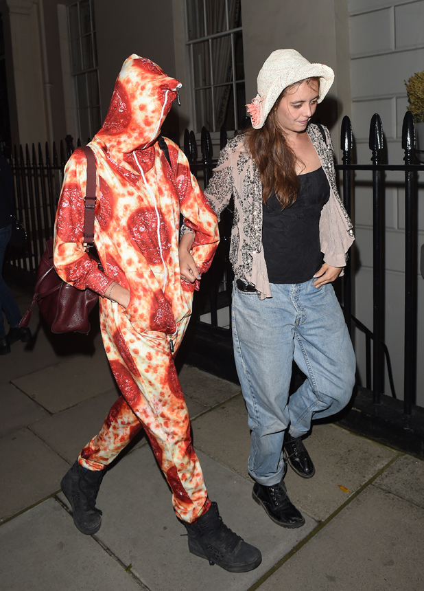 Cara Delevingne arrives back into London from Ibiza wearing a Pepperoni Pizza design Morphsuit. She had been celebrating her 22nd birthday in Ibiza with her sister and friends.