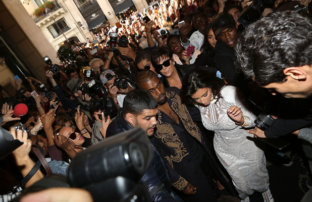 Kim Kardashian and Kanye West are surrounded by fans as they arrive to attend the 'Balmain' fashion show at Paris Fashion Week on September 25, 2014 in Paris, France. (Photo by Marc Piasecki/GC Images)