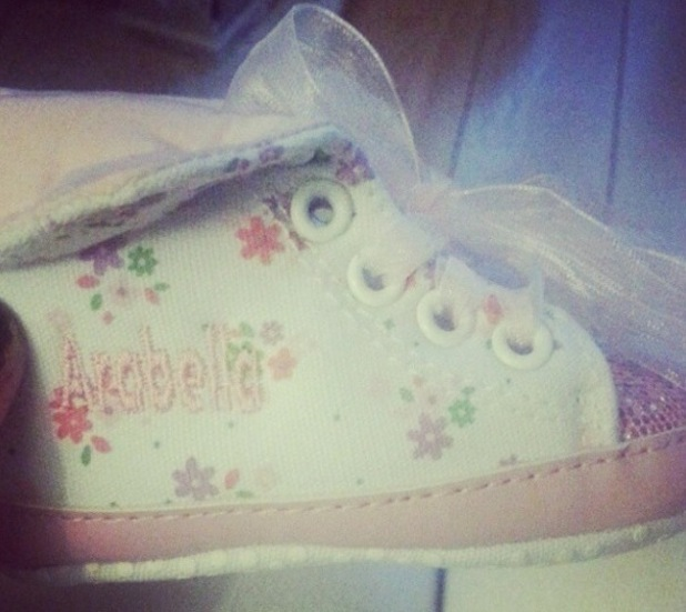 Rebecca Ferguson shows off new baby shoes for her third child, daughter Arabella.