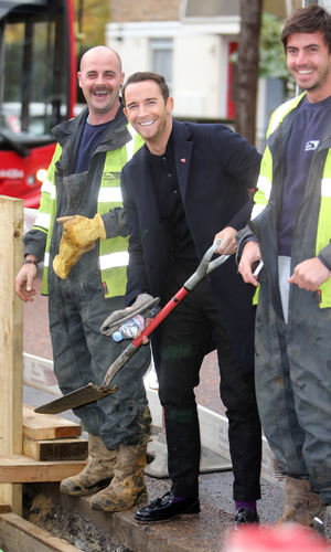 X Factor's Jay James shovels cement with workmen outside the ITV studios. 11/17/2014 London, United Kingdom