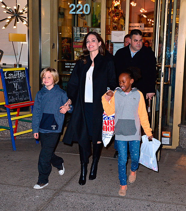 Shiloh Jolie-Pitt, Angelina Jolie and Zahara Jolie-Pitt leave Lee's Art Shop on November 21, 2014 in New York City.