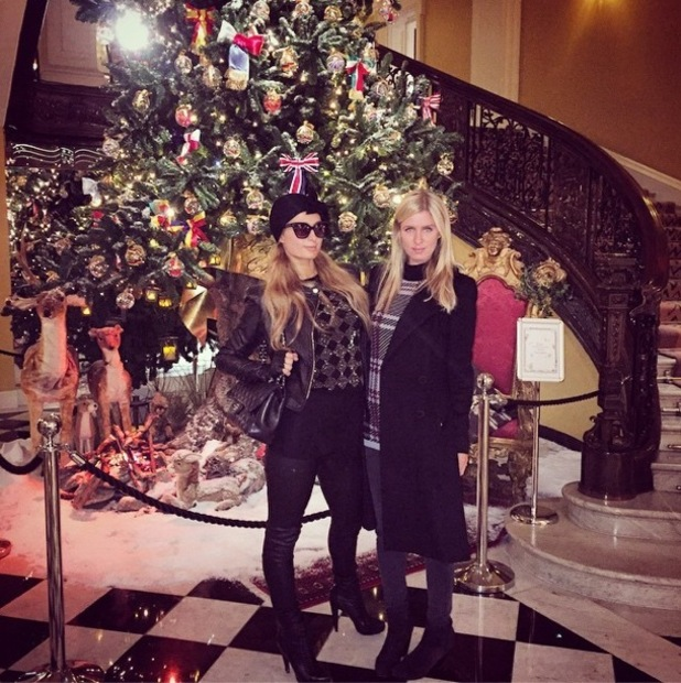 Paris Hilton and Nicky Hilton pose by the Christmas tree in Claridge's hotel in London - 15 December 2014