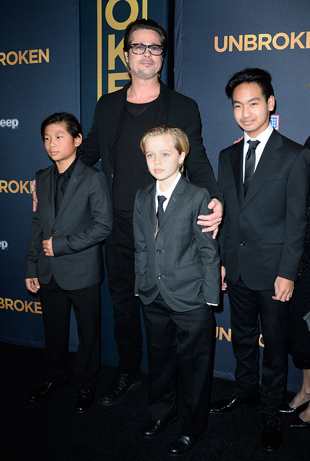 Brad Pitt and children Pax Jolie-Pitt (L), Shiloh Jolie-Pitt (C) and Maddox Jolie-Pitt arrive for the U.S. premiere of Universal Pictures 'Unbroken,' December 15, 2014 at the Dolby Theatre in Hollywood, California.