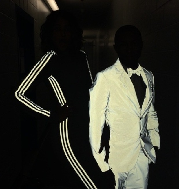 Helen Lasichanh and Pharrell Williams show off reflective Adidas suit at the 57th Annual GRAMMY Awards at the STAPLES Center on February 8, 2015 in Los Angeles, California.