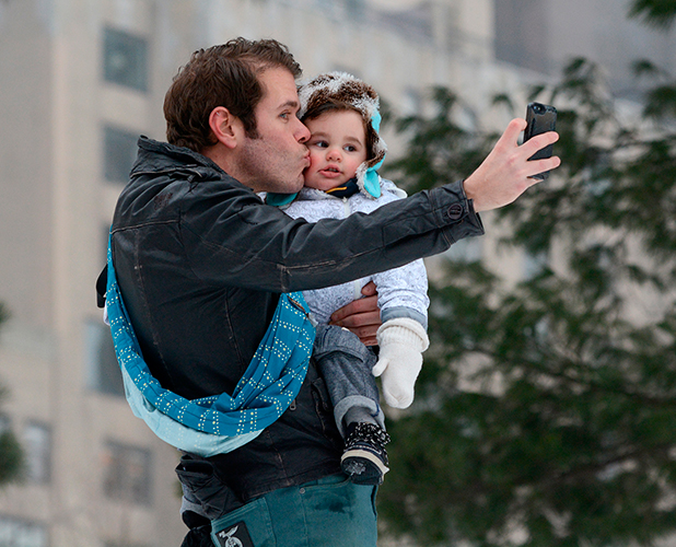 Perez Hilton wearing teddy bear sneakers in a snow covered Central Park out playing with his son, Mario on the swings and slide and sharing a 'selfie' to remember the occasion, 8 February 2015
