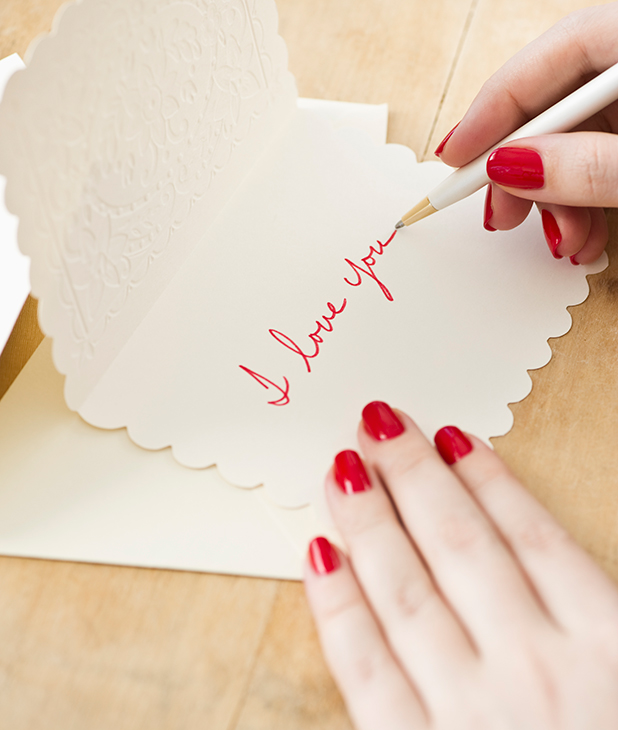 Woman writes a Valentine's Day card, stock image