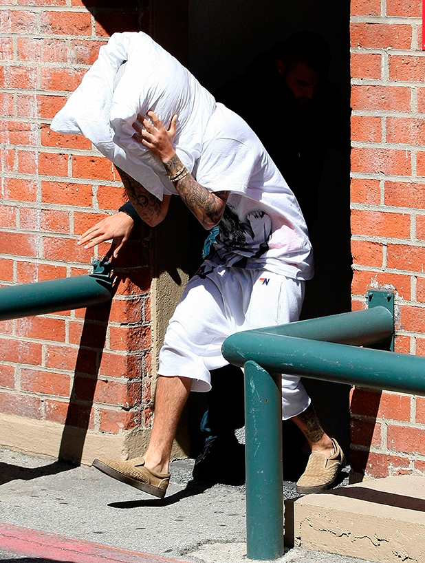 Justin Bieber leaving a building with a pillow wrapped around his head 23 Mar 2015