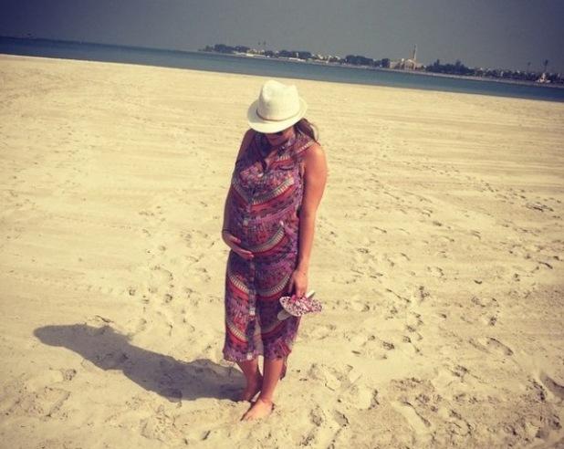 Pregnant Billi Mucklow cradles baby bump on the beach in Abu Dhabi - 1 April 2015.