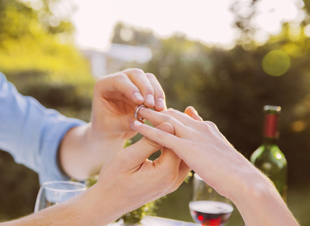 VARIOUS model released Man putting ring on woman's finger at dinner