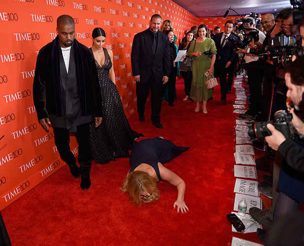 Amy Schumer pretends to trip and fall on the floor in front of honorees Kim Kardashian and Kanye West as they attend the Time 100 Gala celebrating the Time 100 issue of the Most Influential People at The World at Jazz at Lincoln Center on April 21, 2015 in New York.