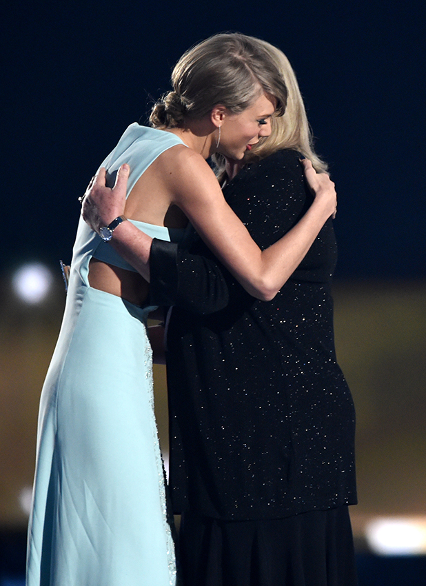 Taylor Swift (L) accepts the 50th Anniversary Milestone Award from Andrea Swift onstage during the 50th Academy Of Country Music Awards at AT&T Stadium on April 19, 2015 in Arlington, Texas.